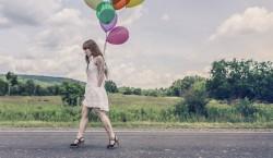 femme marchant sur une route avec des ballons de baudruche accrochés au son bras